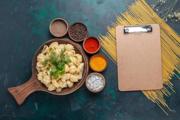 Vue de dessus des pâtes cuites avec bloc-notes et différents assaisonnements sur une surface sombre