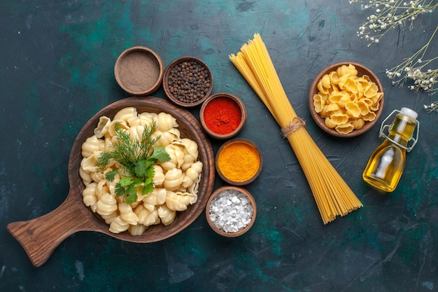 Vue de dessus des pâtes cuites avec différents assaisonnements et huile d'olive sur une surface sombre