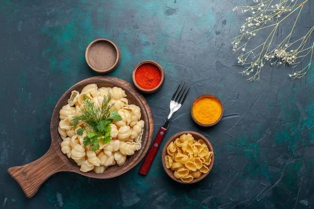 Vue de dessus des pâtes cuites avec des légumes verts et des assaisonnements sur la surface sombre