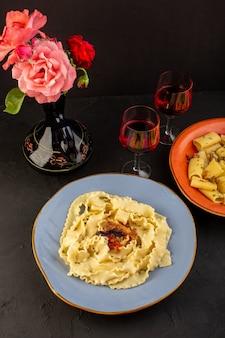 Une vue de dessus des pâtes cuites savoureuses salées à l'intérieur de la plaque bleue ronde avec des verres de vin et de fleurs à l'intérieur de la cruche sur un tapis conçu et un bureau sombre cuisine italienne