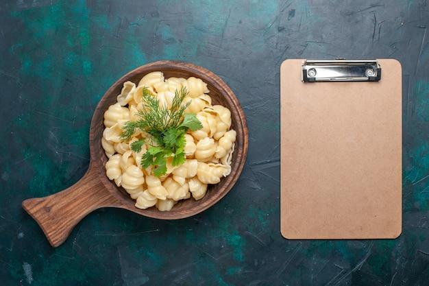 Vue de dessus des pâtes cuites avec des verts et un bloc-notes sur la surface sombre