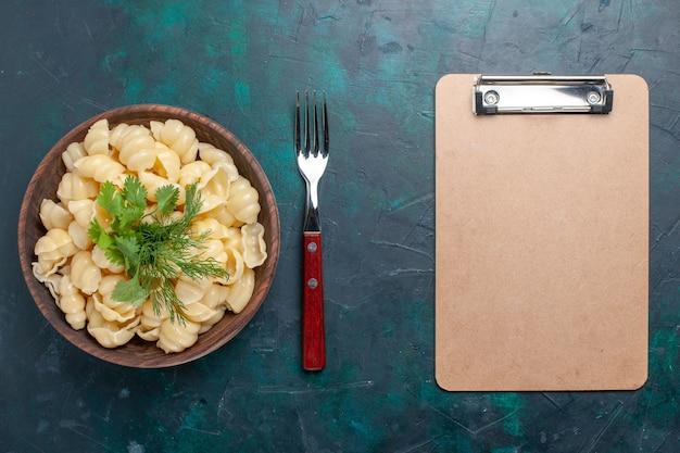 Vue de dessus des pâtes cuites avec des verts à l'intérieur de la plaque et avec bloc-notes sur un bureau sombre