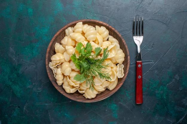 Vue de dessus des pâtes cuites avec des verts à l'intérieur de la plaque sur le bureau sombre
