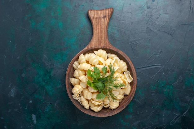 Vue de dessus des pâtes cuites avec des verts à l'intérieur de la plaque sur la surface sombre