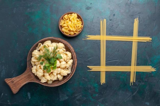 Vue de dessus des pâtes cuites avec des verts sur une surface sombre