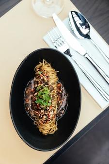 Vue de dessus de pâtes froides capellini aux algues de hikiji, essence de truffes et de homard refroidies, servies dans un bol noir.