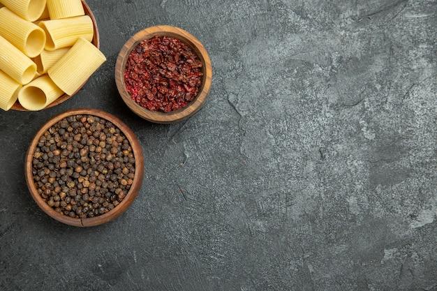 Vue de dessus des pâtes italiennes crues avec des assaisonnements sur le fond gris pâte à pâtes repas épicé cru