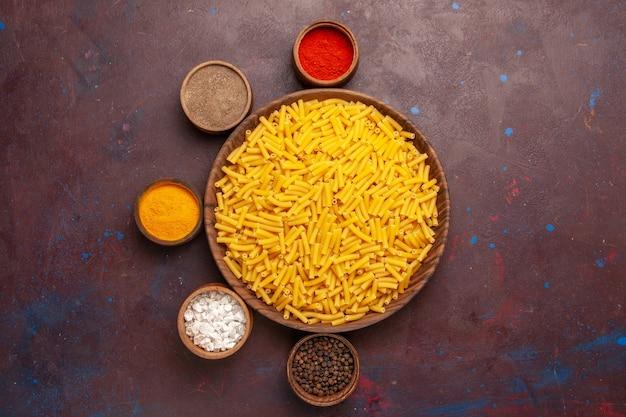 Vue de dessus des pâtes italiennes crues avec des assaisonnements sur la pâte de couleur alimentaire de repas de pâtes de bureau foncé