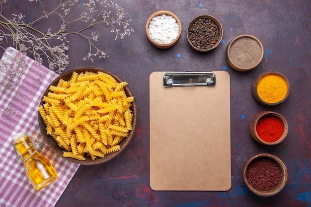 Vue de dessus des pâtes italiennes crues avec différents assaisonnements sur la surface sombre des pâtes alimentaires couleur des ingrédients du repas