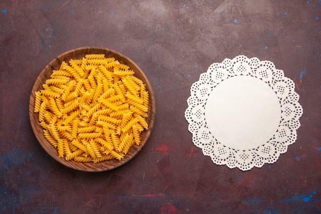 Vue de dessus des pâtes italiennes crues sur fond violet foncé pâtes alimentaires repas crus