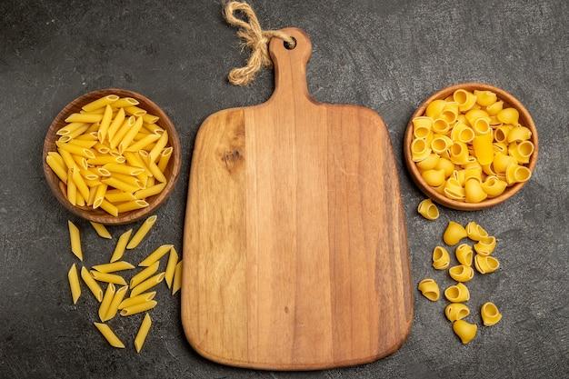 Vue de dessus des pâtes italiennes crues à l'intérieur des assiettes brunes sur le gris