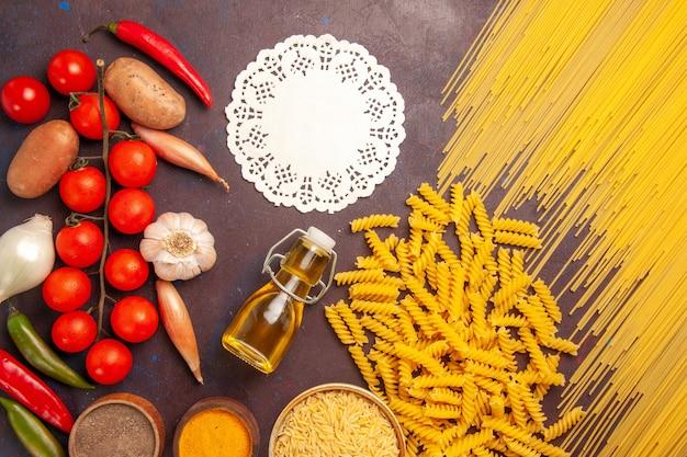 Vue de dessus des pâtes italiennes crues avec des légumes frais et des assaisonnements sur un bureau sombre repas de pâtes alimentaires légume couleur crue