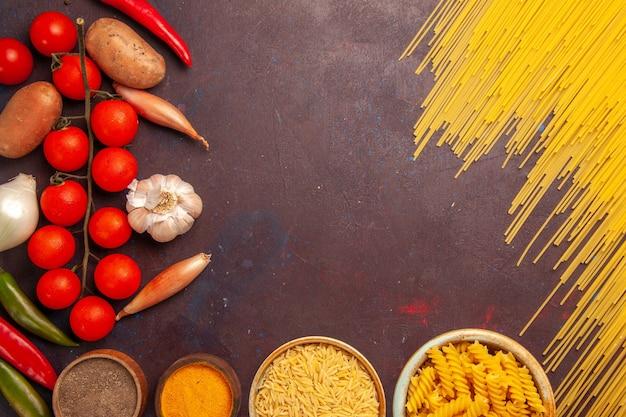 Vue de dessus des pâtes italiennes crues avec des légumes frais et des assaisonnements sur fond sombre couleur pâtes alimentaires italie pâte