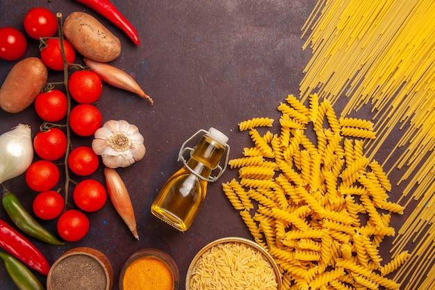 Vue de dessus des pâtes italiennes crues avec des légumes frais et des assaisonnements sur fond sombre repas de pâtes alimentaires légumes de couleur crue