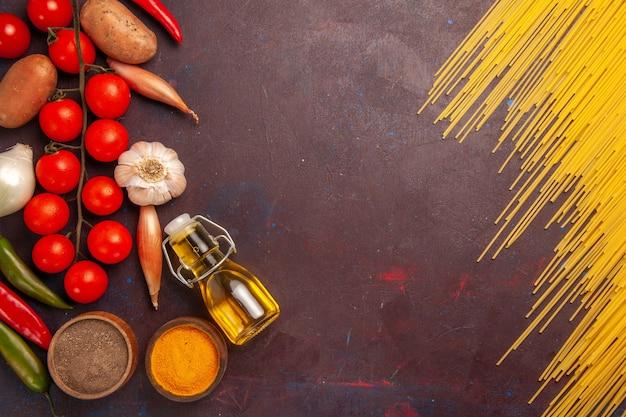 Vue de dessus des pâtes italiennes crues avec des légumes frais et des assaisonnements sur fond violet foncé repas de pâtes alimentaires légume couleur crue