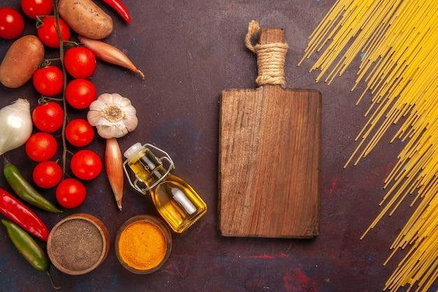 Vue de dessus des pâtes italiennes crues avec des légumes frais et des assaisonnements sur fond violet foncé repas de pâtes alimentaires légumes de couleur crue