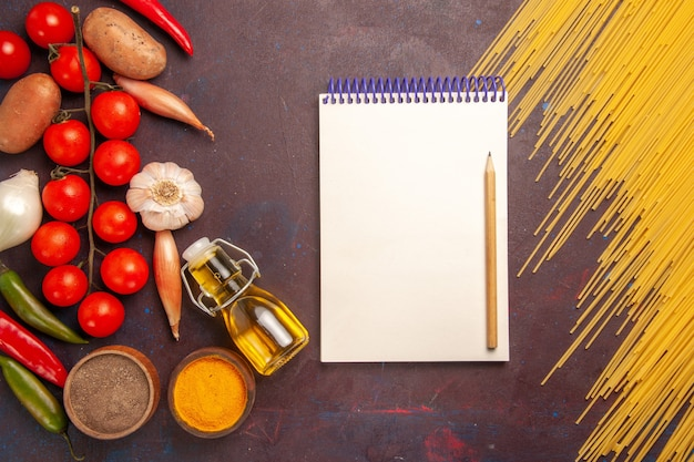 Vue de dessus des pâtes italiennes crues avec des légumes frais et des assaisonnements sur fond violet foncé repas de pâtes alimentaires légumes crus