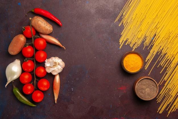 Vue de dessus des pâtes italiennes crues avec des légumes frais et des assaisonnements sur des pâtes repas de bureau sombre couleur alimentaire pâte italie