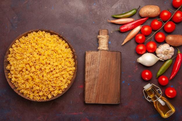 Vue de dessus des pâtes italiennes crues avec des légumes frais sur le fond sombre de la couleur des aliments de repas de pâtes végétales