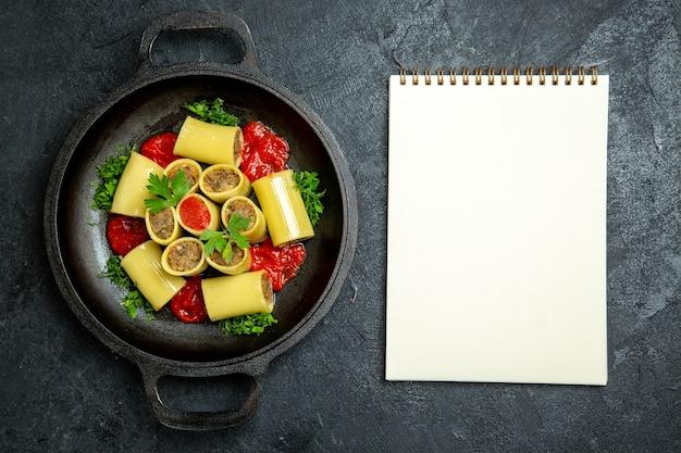Vue de dessus des pâtes italiennes crues avec des légumes verts de viande et de la sauce tomate à l'intérieur de la casserole sur le fond gris foncé de la pâte de pâtes alimentaires repas