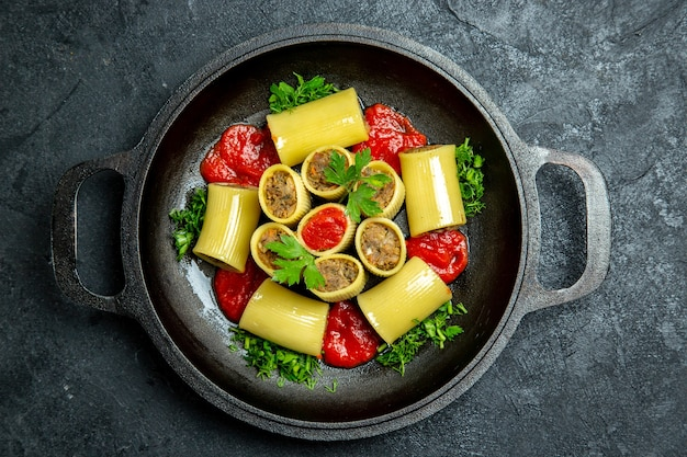 Vue de dessus des pâtes italiennes crues avec des légumes verts de viande et de la sauce tomate à l'intérieur de la casserole sur le fond sombre de la pâte de pâtes alimentaires repas