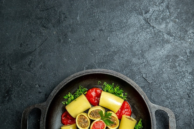 Vue de dessus des pâtes italiennes crues avec des légumes verts de viande et de la sauce tomate à l'intérieur de la casserole sur un fond sombre de la pâte de pâtes repas dîner alimentaire
