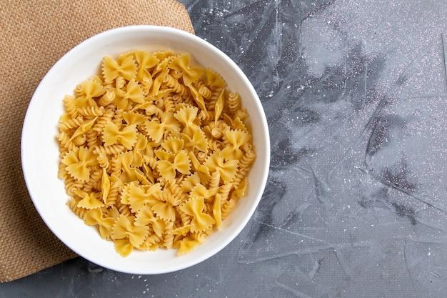 Une vue de dessus des pâtes italiennes crues peu formé à l'intérieur de la plaque blanche sur le bureau gris pâtes repas italien