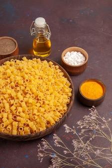 Vue de dessus pâtes italiennes crues peu formé à l'intérieur de la plaque sur le fond sombre pâtes alimentaires dîner de pâte crue beaucoup
