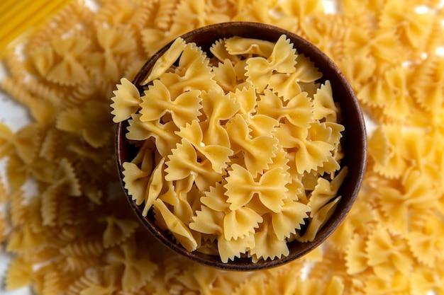 Une vue de dessus des pâtes italiennes crues peu formé avec plaque brune sur le bureau lumineux repas italien de pâtes