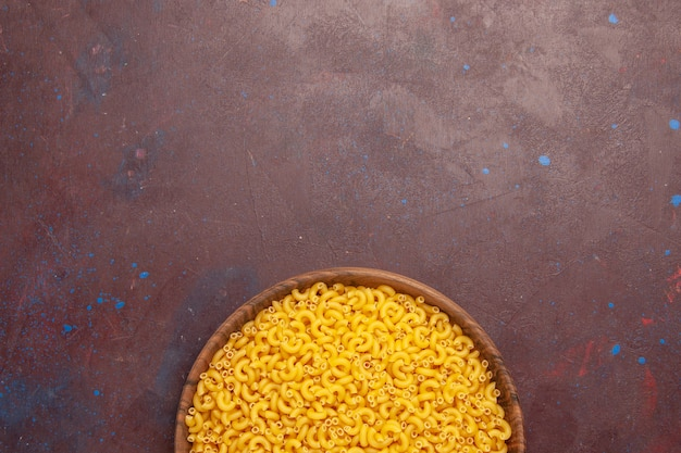 Vue de dessus pâtes italiennes crues peu formées sur fond sombre repas de pâtes alimentaires pâte crue