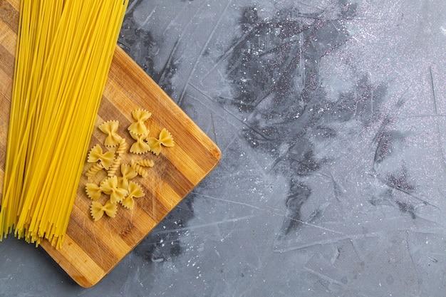 Une vue de dessus des pâtes italiennes crues peu et longtemps formées sur le bureau gris pâtes alimentaires repas italien