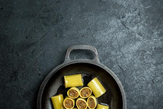 Vue de dessus pâtes italiennes crues avec de la viande à l'intérieur de la casserole sur le fond sombre de la pâte crue repas pâtes alimentaires