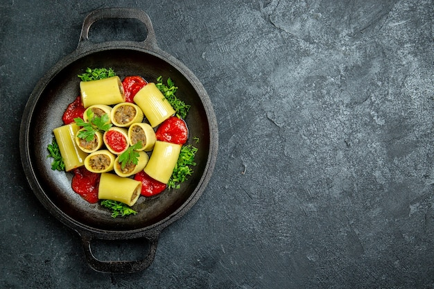 Vue de dessus des pâtes italiennes crues avec de la viande verte et de la sauce tomate à l'intérieur de la casserole sur un bureau sombre de la pâte de pâtes alimentaires