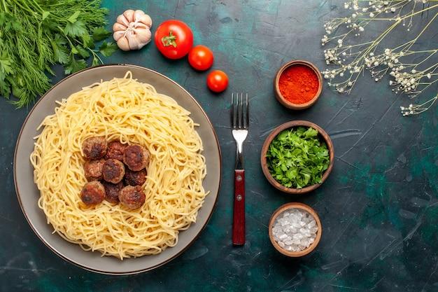 Vue de dessus des pâtes italiennes cuites avec des assaisonnements de boulettes de viande et des légumes verts sur la surface bleu foncé