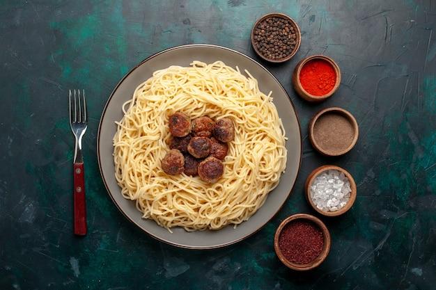 Vue de dessus des pâtes italiennes cuites avec des boulettes de viande et des assaisonnements sur la surface bleu foncé