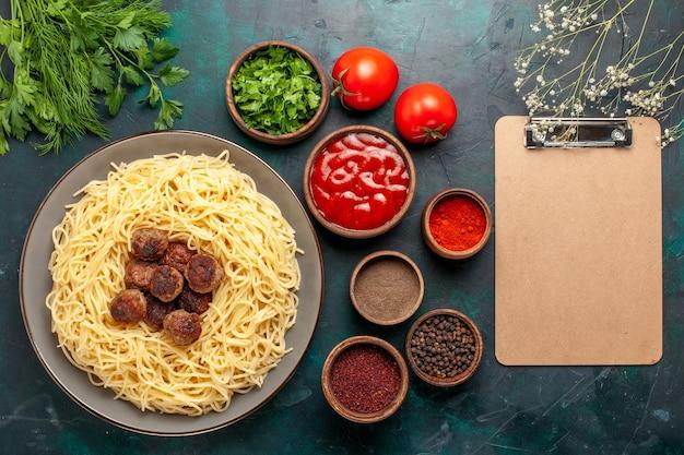 Vue de dessus des pâtes italiennes cuites avec des boulettes de viande et différents assaisonnements sur la surface bleue