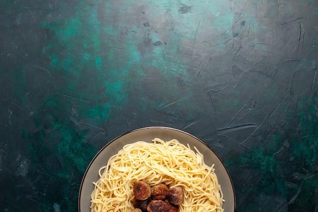 Vue de dessus des pâtes italiennes cuites avec des boulettes de viande sur la surface bleu foncé