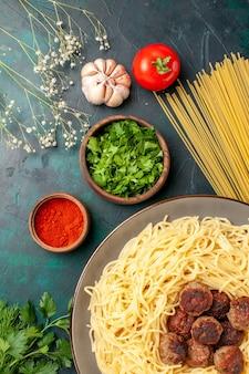 Vue de dessus des pâtes italiennes cuites avec des boulettes de viande et des verts sur la surface bleu foncé