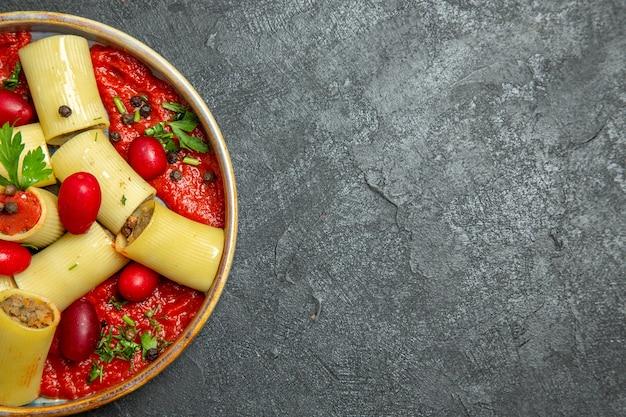 Vue de dessus pâtes italiennes cuites délicieux repas avec de la viande et de la sauce tomate sur le fond gris pâte de pâtes sauce à la viande alimentaire