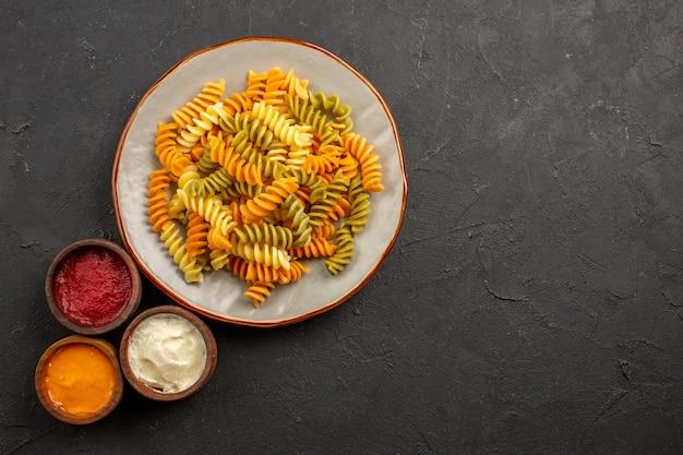 Vue de dessus des pâtes italiennes cuites pâtes en spirale inhabituelles avec des assaisonnements sur l'espace sombre