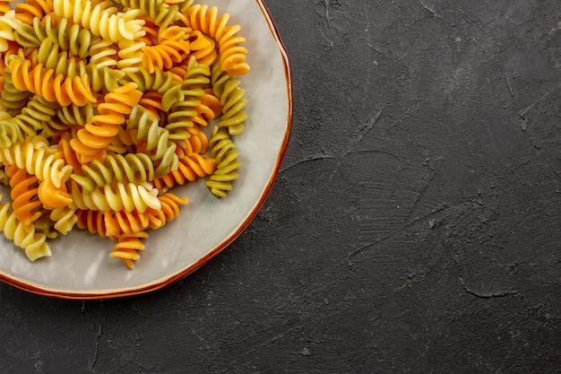 Vue de dessus des pâtes italiennes cuites pâtes en spirale inhabituelles à l'intérieur de la plaque sur l'espace sombre