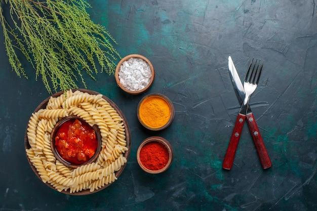 Vue de dessus des pâtes italiennes cuites avec sauce et différents assaisonnements sur une surface bleu foncé