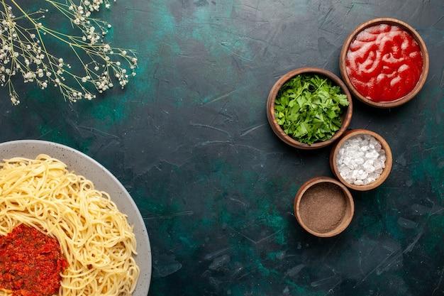 Vue de dessus des pâtes italiennes cuites avec de la viande et différents assaisonnements sur la surface bleu foncé