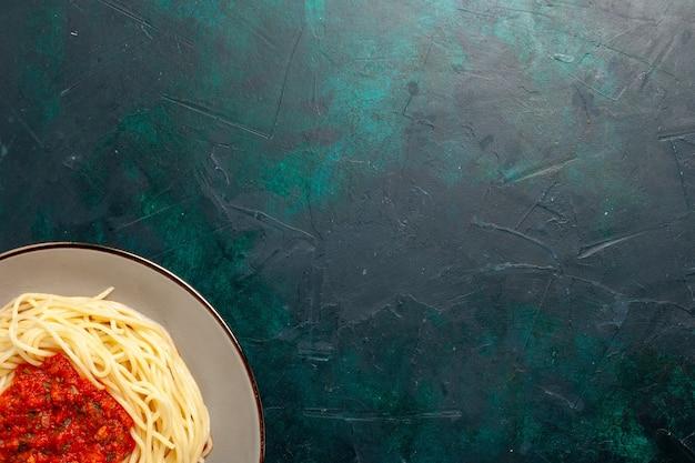 Vue de dessus pâtes italiennes cuites avec viande hachée et sauce tomate sur la surface bleu foncé