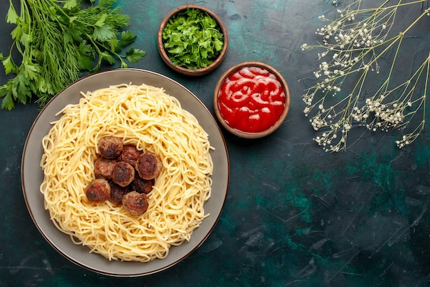 Vue de dessus des pâtes italiennes cuites à la viande sauce tomate et verts sur la surface bleu foncé