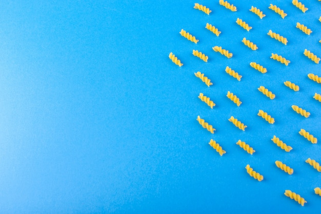 Une vue de dessus des pâtes jaunes brutes isolées doublées de pâtes italiennes sèches sur le fond bleu des repas spaghetti