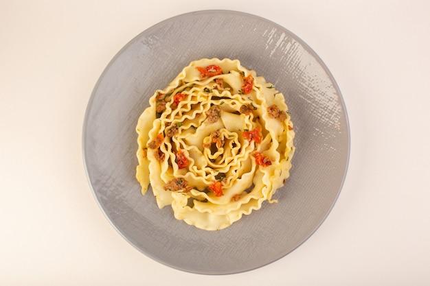 Une vue de dessus des pâtes avec des légumes tranchés cuits et de la viande à l'intérieur de la plaque grise sur blanc