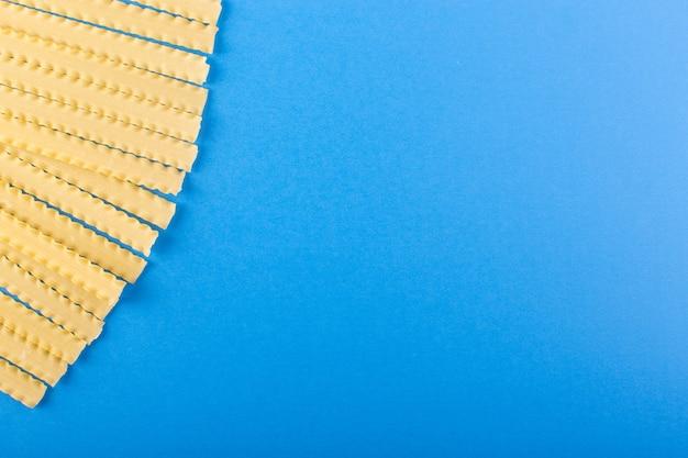 Une vue de dessus pâtes longues italiennes jaune cru bordée sur le bleu
