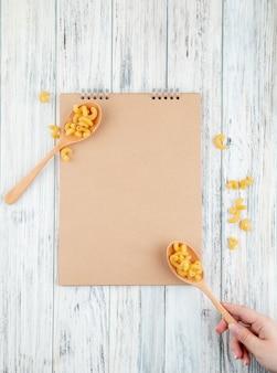Vue de dessus des pâtes macaroni au coude sur une cuillère sur fond de bois blanc