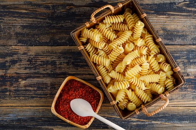 Vue de dessus des pâtes macaroni dans un bac avec du poivron rouge, une cuillère sur fond de bois. espace horizontal pour le texte